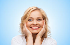 Smiling woman in white t-shirt touching her face Stock Photo