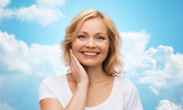 Smiling woman in white t-shirt touching her face Royalty Free Stock Photo
