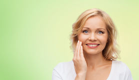 Smiling woman in white t-shirt touching her face Stock Image