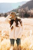 Smiling Woman in White Winter Jacket Wearing Brown Cowboy Hat Surrounded of Brown Grass Field Stock Image