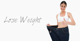 Smiling woman who lost a lot of weight the thumbup Stock Photo