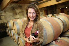 Smiling woman in wine cellar with bottle of wine Royalty Free Stock Photo