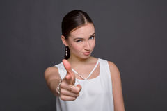 Smiling woman wink and pointing to camera Stock Image