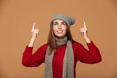 Smiling woman in winter clothes pointing with finger and looking Stock Image