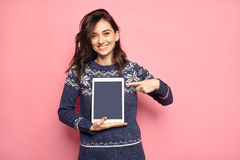 Smiling woman in winter clothes pointing to tablet screen Stock Photo