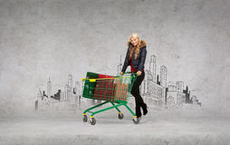 Smiling woman in winter clothes with shopping car Stock Images