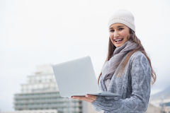 Smiling woman with winter clothes on using her laptop Stock Photography
