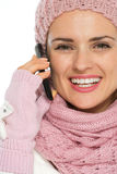 Smiling woman in winter clothing speaking mobile Royalty Free Stock Photography
