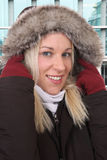 Smiling woman in winter with warm clothing outdoor in town Stock Image