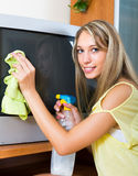 Smiling woman  wiping the dust on TV Stock Photography