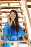 Smiling woman on wooden stairs Stock Photo
