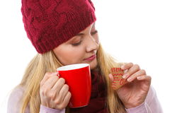 Smiling woman in woolen cap and shawl with gingerbread cookies and tea, white background, christmas time Stock Photo