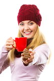 Smiling woman in woolen cap and shawl with gingerbread cookies and tea, white background, christmas time Stock Photos