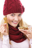 Smiling woman in woolen cap and shawl holding gingerbreads, christmas time Stock Image