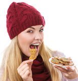 Smiling woman in woolen cap and shawl holding gingerbreads, christmas time Stock Images
