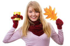 Smiling woman in woolen gloves with decorated cup of tea and autumnal leaf, autumn decoration Royalty Free Stock Photo