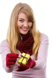 Smiling woman in woolen gloves opening gift for Christmas or other celebration Stock Photos