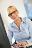Smiling woman at work in front of desktop Royalty Free Stock Photography