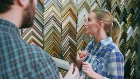 Smiling woman worker chatting with male customer about picture frame details near stand in frame atelier stock video