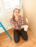 Smiling woman worker holding spatula and putty Royalty Free Stock Images