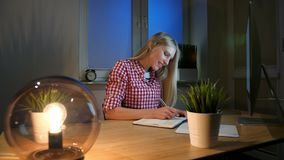Smiling woman working on computer at night. Smiling female in checkered shirt sitting at lit by small lamp wooden desk stock video footage