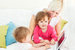 Smiling woman working with her children on laptop royalty free stock images