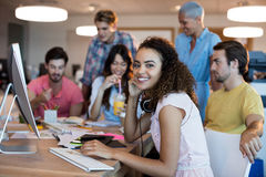 Smiling woman working with her team in office Stock Photo