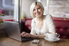 Smiling woman working with laptop computer in cafe Royalty Free Stock Image