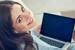 Smiling woman working with laptop at home. Stock Photography