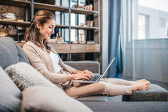 Smiling woman working on laptop while relaxing on sofa at home Stock Image