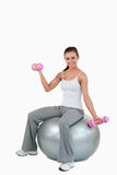 A smiling woman working out with dumbbells. Portrait of a smiling woman working out with dumbbells and a ball against a white background Stock Photos