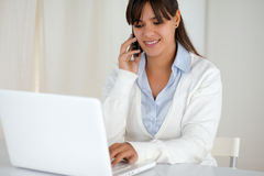 Smiling woman working and speaking on cellphone Stock Photo