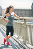 Smiling woman in workout gear standing on a bridge Stock Image