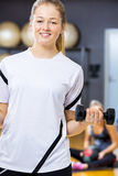 Smiling woman in workout outfit holds dumbbell at fitness gym Stock Photos