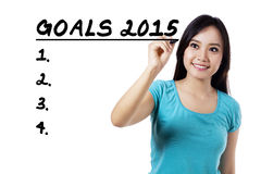 Smiling woman writes her goals Royalty Free Stock Photos