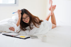 Smiling woman writing notes lying in bed Royalty Free Stock Image