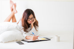 Smiling woman writing notes lying in bed Royalty Free Stock Photo