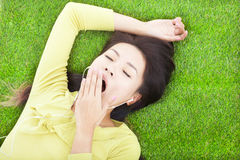 Smiling  woman yawning  and lying on grass Stock Photography