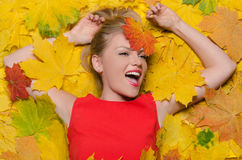 Smiling woman in yellow autumn leaves Royalty Free Stock Photography