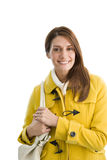 Smiling woman in yellow coat holding purse Stock Images