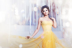Smiling woman in yellow evening dress and with Royalty Free Stock Photos