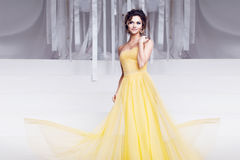 Smiling woman in yellow evening dress and with Stock Photos