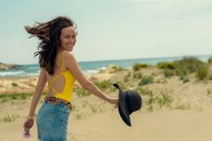 A woman in a yellow swimsuit and denim shorts walking on the beach royalty free stock photography