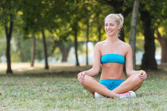 Smiling woman during yoga exercises in the park Stock Photo