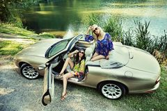Smiling women. In a convertible car stock photo