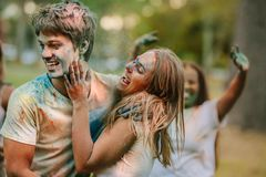 Couple having fun playing holi in a park with friends royalty free stock image