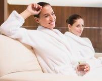 Smiling women in bathrobes drinking water Stock Photo