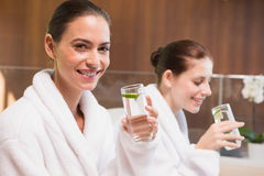 Smiling women in bathrobes drinking water Stock Image