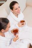 Smiling women in bathrobes having tea Royalty Free Stock Image