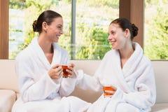Smiling women in bathrobes having tea Royalty Free Stock Photos